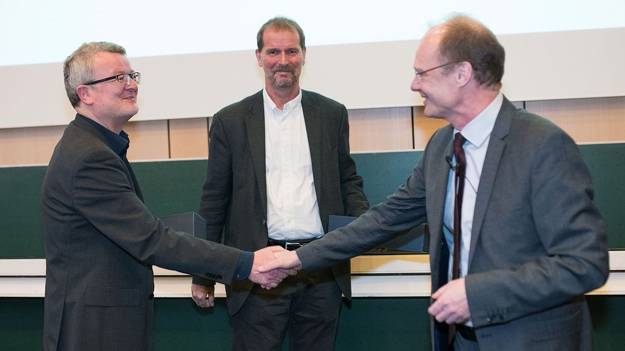 President Weber shaking hands and congratulating two leading scientists of Ulm University