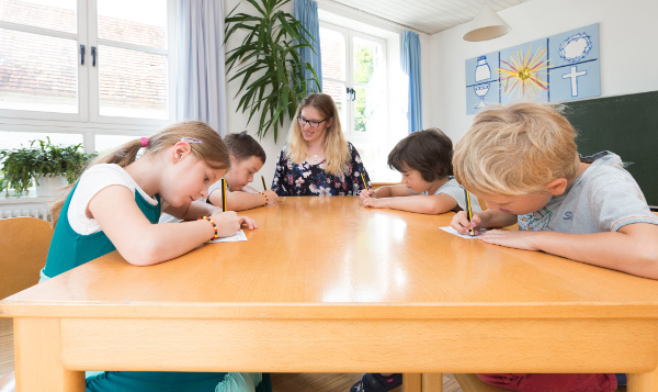 Children writing with a pencil